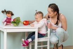 有婴孩的母亲在厨房里。 免版税库存照片