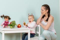 有婴孩的母亲在厨房里。 免版税图库摄影
