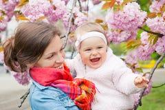 有婴孩的母亲在庭院里 免版税库存照片