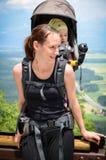 有婴孩的母亲背包载体的在山步行 库存图片