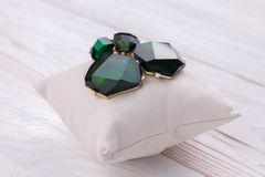 有绿宝石的金耳环在枕头 免版税库存照片