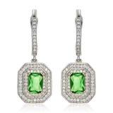 有绿宝石的银色耳环在白色 免版税库存照片