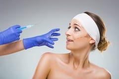 有整容手术的美丽的妇女,对针,一位整形外科医生手的恐惧 库存照片