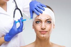 有整容手术的美丽的妇女,拿着针的整形外科医生 免版税库存图片