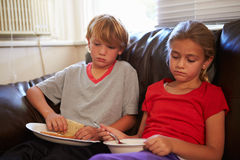 有贫寒饮食的孩子在家吃在沙发的膳食 图库摄影
