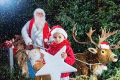 有他小的帮手和他的驯鹿的圣诞老人 免版税库存图片