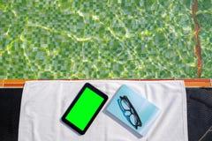 有黑屏和蓝皮书的片剂与说谎在游泳池边的白色毛巾的玻璃 免版税库存图片