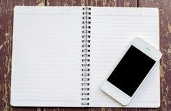 有黑屏幕和开放笔记本的白色巧妙的电话在老dir 库存图片