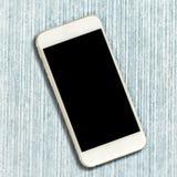 有黑屏幕的白色智能手机在蓝色木背景 免版税库存照片