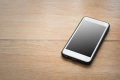 有黑屏的巧妙的电话在木背景 库存图片