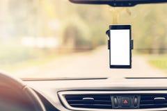 有黑屏的手机在汽车挡风玻璃持有人 库存图片