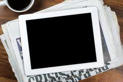 有黑屏的数字式片剂在报纸 图库摄影