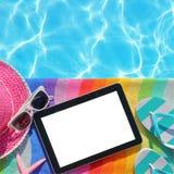 有黑屏的片剂由游泳池边 库存图片
