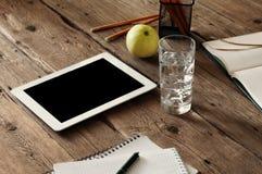 有黑屏的白色片剂计算机在木桌上 免版税库存照片