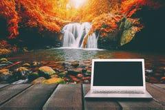 有黑屏的膝上型计算机在与瀑布的木桌上 免版税图库摄影