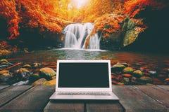 有黑屏的膝上型计算机在与瀑布的木桌上 库存图片