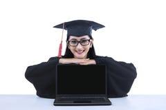有黑屏膝上型计算机的亚洲人毕业生 库存照片