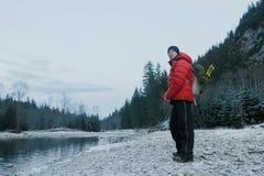 有登山家的休息的登山家挑运和站立在小卵石河岸的设备在平衡岩石风景的冬天 库存照片