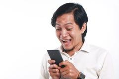 有他巧妙的电话的惊奇的亚裔人 库存图片