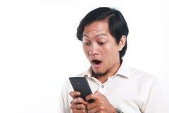 有他巧妙的电话的震惊亚裔人 免版税库存图片