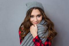 有围巾和帽子的微笑的逗人喜爱的妇女 免版税库存图片