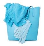 有围巾和手套的蓝色夫人提包,被隔绝 免版税库存照片