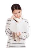 有围巾的美丽的亚裔女孩读了一本哀伤的书 免版税图库摄影