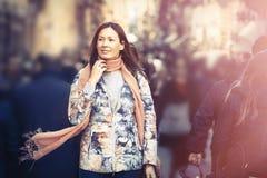 有围巾的美丽的妇女走在人群城市的 时数横向季节冬天 图库摄影