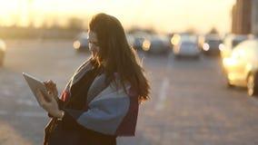 有围巾的年轻微笑的妇女使用片剂计算机户外在停车场 奇妙日落 缓慢的mo 影视素材