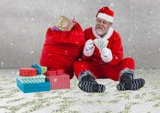 有货币的愉快的圣诞老人在圣诞节礼物旁边注意坐 库存照片