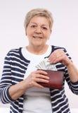 有货币的美元,金融证券的概念愉快的资深女性举行的钱包在晚年的 库存图片