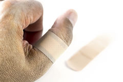 有绷带的拇指在白色背景 免版税库存图片