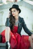 有黑帽会议、红色摆在坐台阶的礼服和起动的美丽的妇女 在秋天期间的年轻深色的消费的时间 库存照片