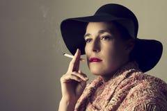 有黑帽会议的成熟妇女坐抽烟 免版税库存图片