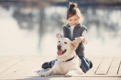 有他心爱的狗的小女孩在湖 库存照片
