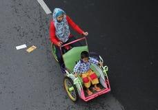有任意乘坐在独奏汽车d的一个小孩子的一个母亲一辆人力车 库存图片