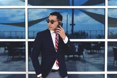 有年轻成功的聪明的人的企业家电话谈话,当站立近的办公室窗口户外时 免版税库存图片