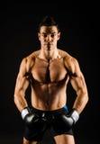有黑手套的年轻坚强的拳击手 免版税图库摄影