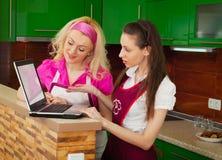 有寻找一份食谱的膝上型计算机的两名妇女在互联网 免版税库存照片