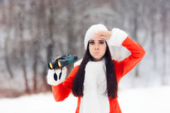 有寻找圣诞节的双筒望远镜的惊奇的冬天妇女 免版税图库摄影