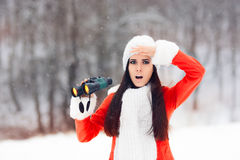 有寻找圣诞节的双筒望远镜的惊奇的冬天妇女 免版税库存图片