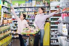 有寻找食物的女孩的妇女在超级市场 免版税库存图片