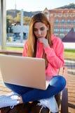 有寻找netbook屏幕的震惊忧虑面孔的少年女孩,读新闻 库存照片