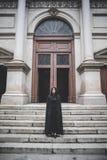 有黑披风和敞篷的美丽的黑暗的吸血鬼妇女 免版税图库摄影