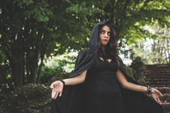 有黑披风和敞篷的美丽的黑暗的吸血鬼妇女 免版税库存照片