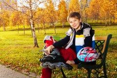 有直排轮式溜冰鞋的愉快的男孩在公园 免版税库存照片