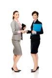 有给握手的笔记本的两名妇女 免版税图库摄影