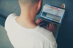 有财政信息的商人坐的前面开放便携式计算机作为图表和图 免版税库存图片