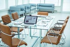 有财政图和纸的开放便携式计算机在桌面上延长在开始企业交涉前 免版税库存照片