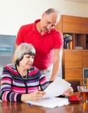 有读财政文件的丈夫的严肃的成熟妇女 库存照片